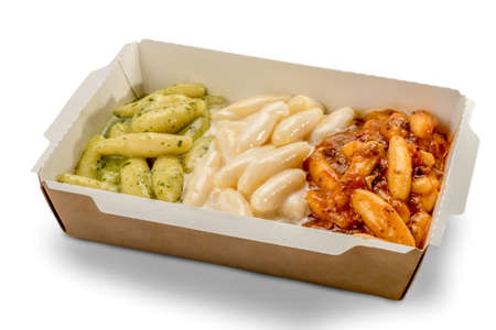 potato gnocchi in a take-away cardboard box topped with tomato sauce, melted cheese and Genoese pesto. Green white and red pasta mimic the Italian flag