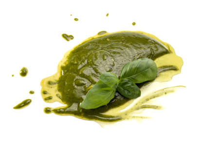 Pesto spread on a white background, typical Genoese and Ligurian sauce, with fresh green basil leaves and extra virgin olive oil Archivio Fotografico
