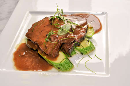 Braised veal in red Barolo wine with a side dish of zucchini and sprouts, in a white plate in top view Banque d'images
