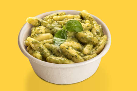 Gnocchi with Genoese pesto sauce in takeaway cardboard plate, isolated on yellow background