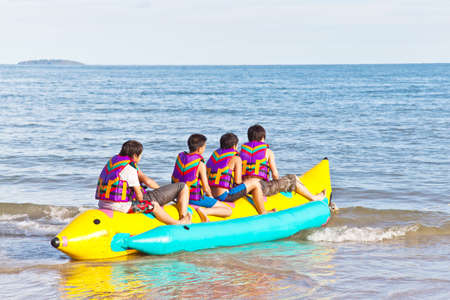 stimulating: group of young people riding banana boat