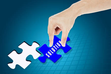 Hand inserting missing solution jigsaw puzzle photo