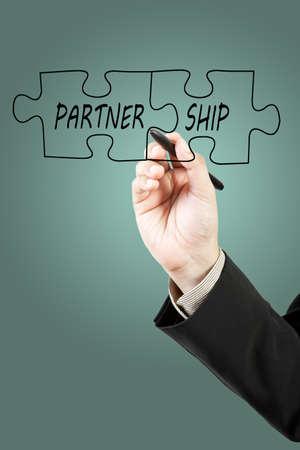 Businessman drawing partnership puzzle pieces photo