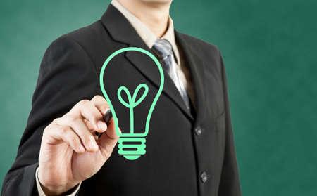 Businessman drawing light bulb green concept photo
