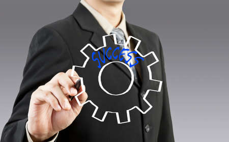 Businessman drawing gear to success photo