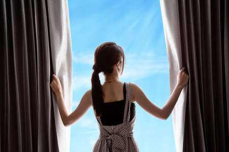 young woman opening curtains and blue sky photo