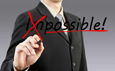 Motivation concept  Businessman changing the word impossible into possible photo