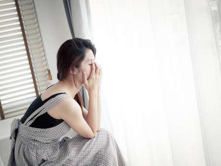 ragazza depressa: donna triste seduta da sola in camera Archivio Fotografico
