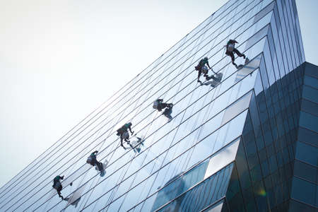property management: group of workers cleaning windows service on high rise building Stock Photo