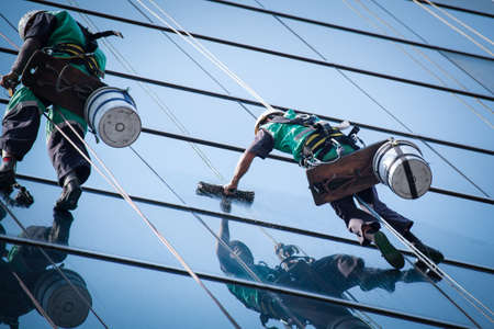 group of workers cleaning windows service on high rise building Editorial