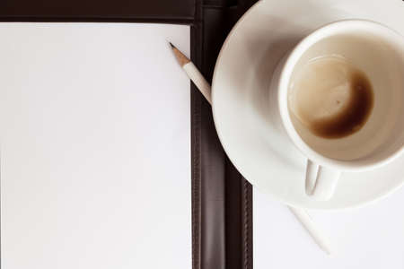 blank white notebook, pen and cup of coffee photo