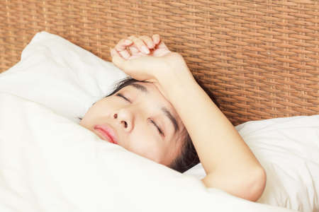 woman with headache lying on bed photo