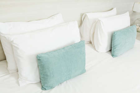 bedder: White and green pillows on bed