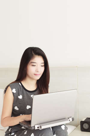 Young Asian woman playing internet on notebook and smiling photo