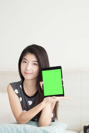 Young Asian woman show or display tablet with green screen photo