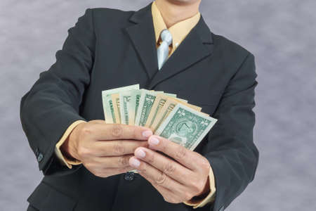 Businessman holding Money Cash Dollars in hands, finance concept photo