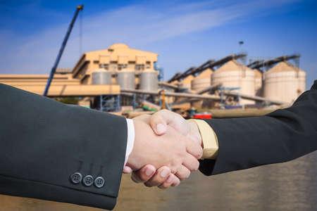 Businessman handshake with silo transportation logistic background photo
