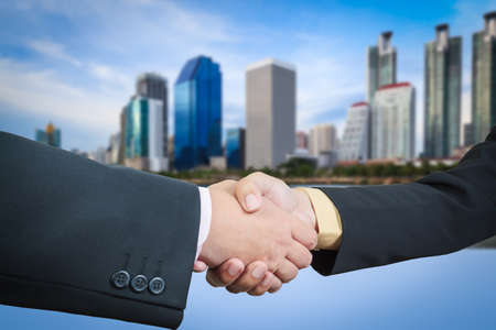 Businessman handshake with building area background photo