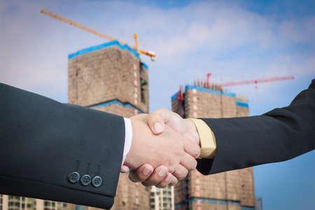 Businessman handshake with building construction background photo