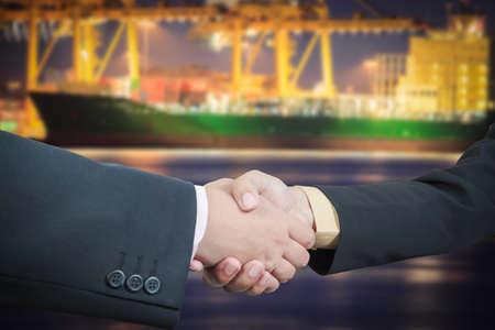 Businessman handshake with ship transportation logistic background photo