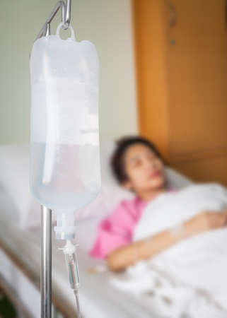 saline: Infusion bottle with saline solution for patient in hospital room Stock Photo