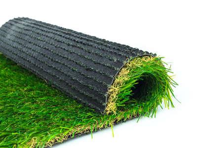 pasto sintetico: El césped artificial césped verde rollo en el fondo blanco Foto de archivo