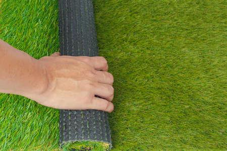 pasto sintetico: El c�sped artificial rollo de hierba verde con la mano