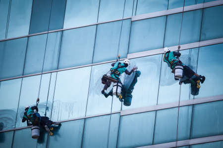 group of workers cleaning windows service on high rise building Stock Photo