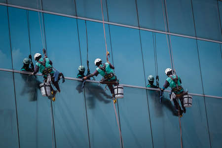 group of workers cleaning windows service on high rise building photo