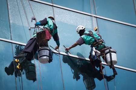 clean window: group of workers cleaning windows service on high rise building Stock Photo