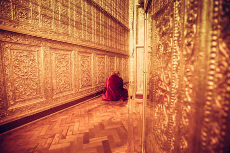 meditation room: MYANMAR - FEBRUARY 9: Unidentified Monk in Red suit make meditation in big golden room at Botataung pagoda on February 09, 2014 in Yangon, Myanmar