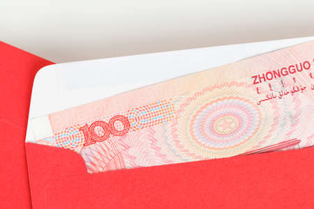 Chinese or 100 Yuan banknotes money in red envelope, as chinese new year background photo
