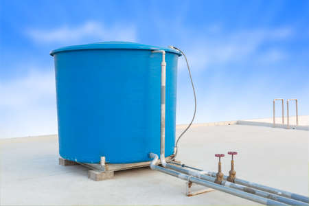Blue water tank of industrial building on roof top and blue cloud sky background