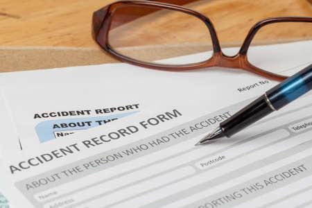 accidente laboral: Formulario de solicitud de informe de accidentes y la pluma en el sobre y gafas marr�n, seguros de empresas y el concepto de riesgo; documento es maqueta