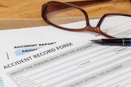 elementos de protecci�n personal: Formulario de solicitud de informe de accidentes y la pluma en el sobre y gafas marr�n, seguros de empresas y el concepto de riesgo; documento es maqueta