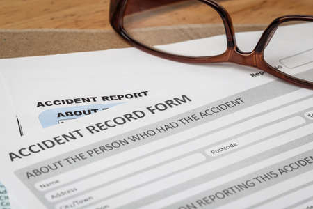 at home accident: Accident report application form on brown envelope and eyeglass, business insurance and risk concept; document is mock-up