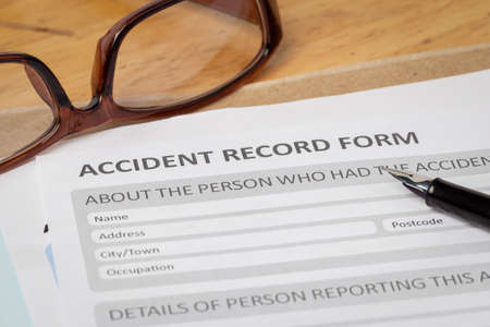 insure: Accident report application form and pen on brown envelope and eyeglass business insurance and risk concept document is mockup