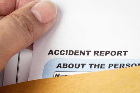 accidente trabajo: Formulario de solicitud de informe de accidentes y la pluma en el sobre y gafas marr�n, seguros de empresas y el concepto de riesgo; documento es maqueta