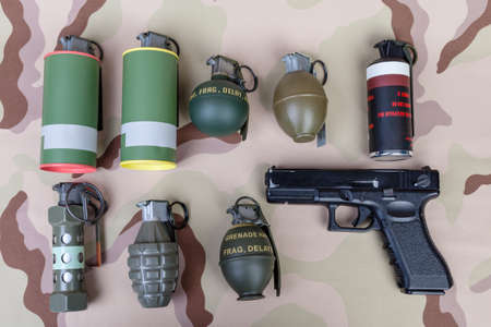 frag: All explosives, weapon army,standard time fuze, hand grenade and gun on camouflage background, top view