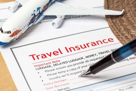 Travel Insurance Claim application form and hat with eyeglass and pen on brown envelope, business insurance and risk concept; document and plane is mock-up 写真素材