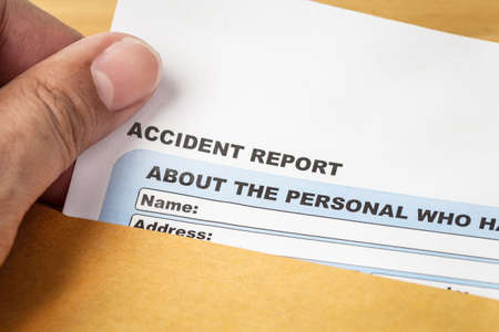 accidente laboral: Formulario de solicitud de informe de accidente y de la mano del hombre en el sobre marr�n, seguros de empresas y el concepto de riesgo; documento es maqueta