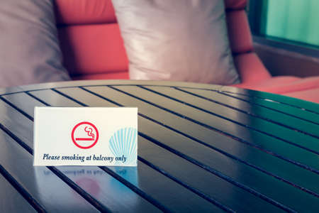 to designate: Smoking Area at balcony only, wording sign on table Stock Photo