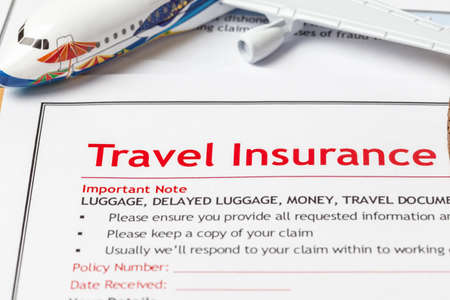 travel agent: Travel Insurance Claim application form on brown envelope, business insurance and risk concept; document and plane is mock-up Stock Photo