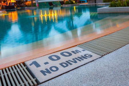 no diving sign: warning sign 1.00m No Diving at Swimming pool of luxury hotel Stock Photo