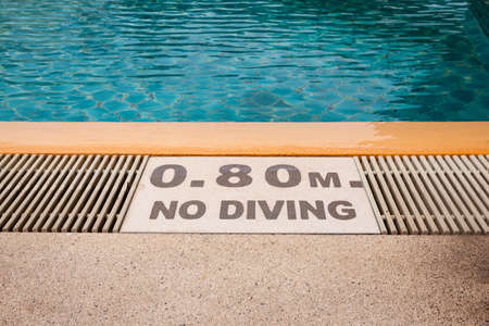 warning sign 0.80m No Diving at Swimming pool of luxury hotel Stock Photo