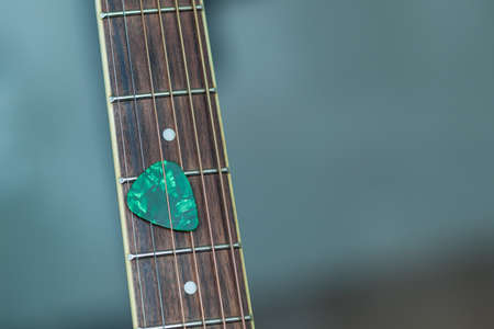 guitar pick: colorful green guitar pick on finger board, as abstract background