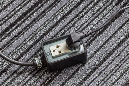 electrical safety: Electrical socket with power plug cable on carpet floor for safety concept Stock Photo