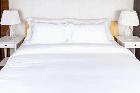 twee kussen op slaapkamer met een wit laken en lamp