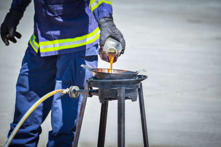 conflagration: fire trainer teach pouring oil into pan flames for conflagration preventive extinguish, safety concept Stock Photo
