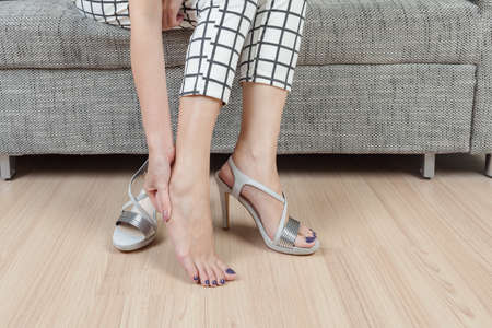 woman sit on chair and female hand with foot pain after, take shoes off Standard-Bild